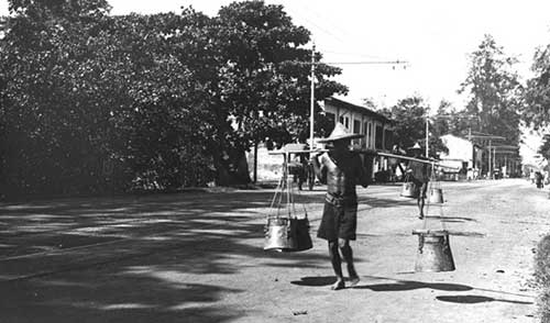 Night Soil Man - When full, a night soil man collected the buckets to dispose of their contents  Courtesy of National Archives of Singapore